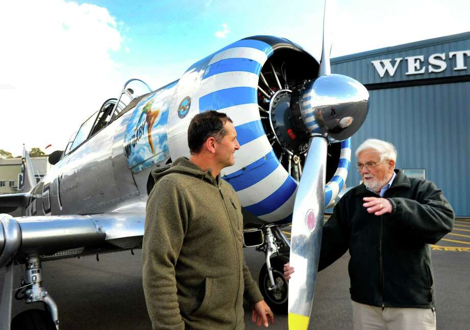 John Plecity Sr., 87, who last flew a Texan P-6 airplane in 1947, takes flight in a P-6 at Danbury Airport. He talks before the flight with pilot Chris Orifici, left, in Danbury, Conn. Thursday, Oct. 24, 2013. Plecity was a radio operator and gunner on a B-17 bomber during World War II. Photo: Michael Duffy / The News-Times