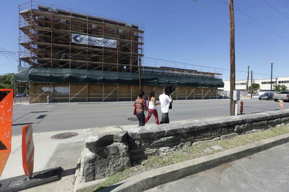 Pedestrians walk north on S. Flores next to the historic wall, right, and in front of the HEB Culinary School which is under construction, left. Photo: BOB OWEN, San Antonio Express-News / © 2012 San Antonio Express-News