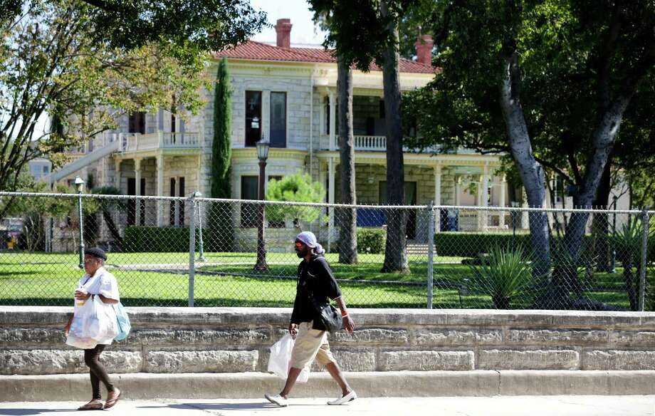Pedestrians walk along the historic wall on Flores St. in front of the Commander's House on HEB's headquarter property between Cesar Chavez and Arsenal. Wednesday, Oct. 23, 2013. Photo: Bob Owen, San Antonio Express-News / ©2013 San Antonio Express-News