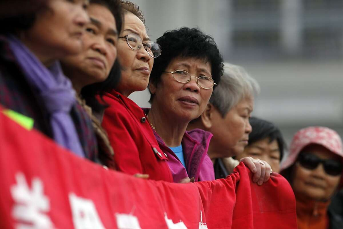 Pei Juan Zheng, center, listens as she stands with other members of the S.F. Community Tenants Association on the steps of San Francisco City Hall to present a comprehensive Speculation Control Agenda to address an eviction epidemic, Thursday October 24, 2013, in San Francisco, Calif.