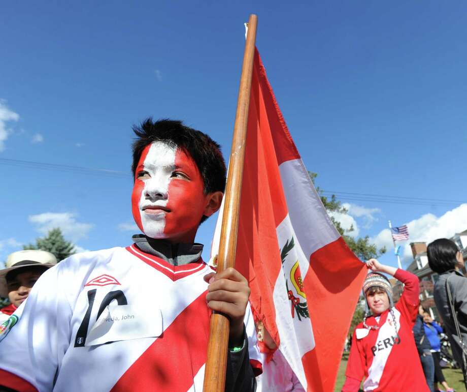 With his face painted in Peruvian red and white, Julian Curtiss school fifth-grader, John Castaneda, 10, carries the flag of Peru during the annual United Nations Day parade at the school in Greenwich, Thursday, Oct. 24, 2013. Photo: Bob Luckey / Greenwich Time