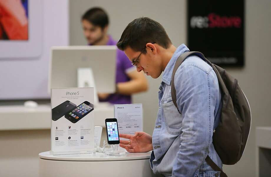A shopper in Moscow looks over a new iPhone 5, which some analysts say won't compete well in Russia with Samsung's lower-price smartphones. Photo: Andrey Rudakov, Bloomberg