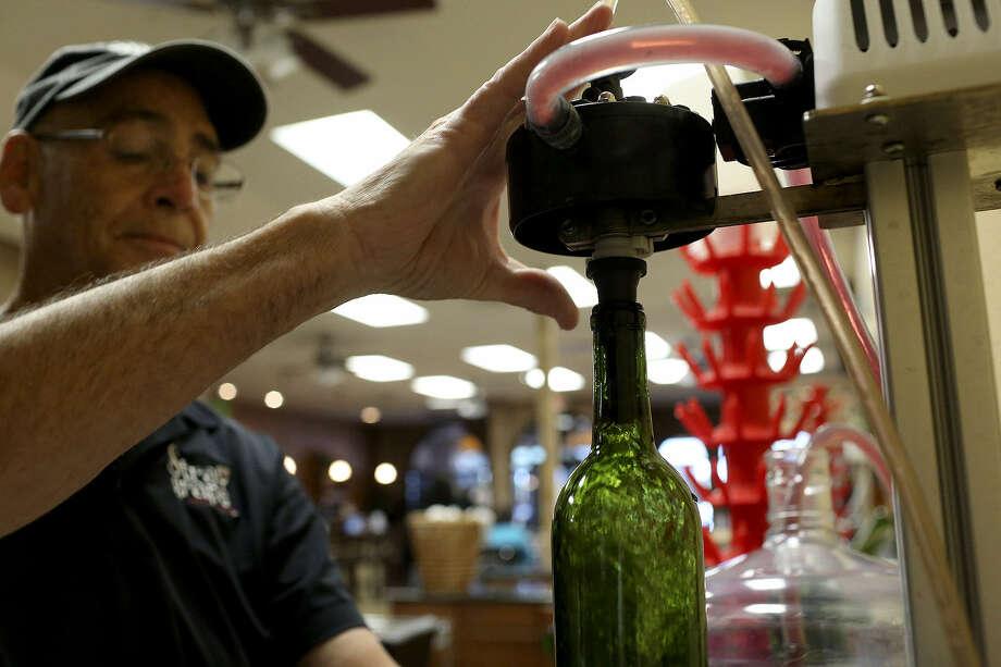 Manager Dennis Jacks bottles cranberry Chianti at Stray Grape Urban Winery. The process takes six to eight weeks. Photo: Photos By Lisa Krantz / San Antonio Express-News