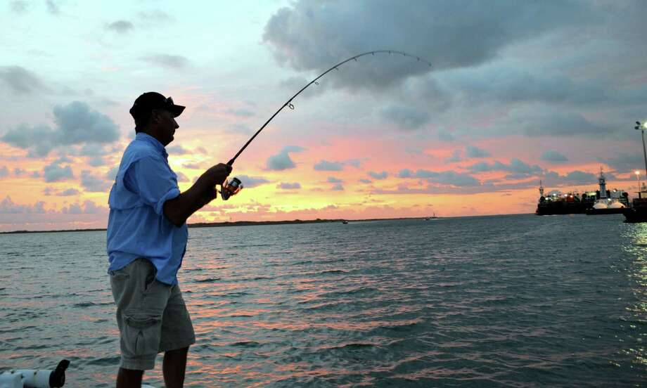 Guide Doug Stanford sets a hook into a flounder that was lying along the rocky bank of the channel near a docked barge. Photo: Photos By Ralph Winingham / For The Express-News