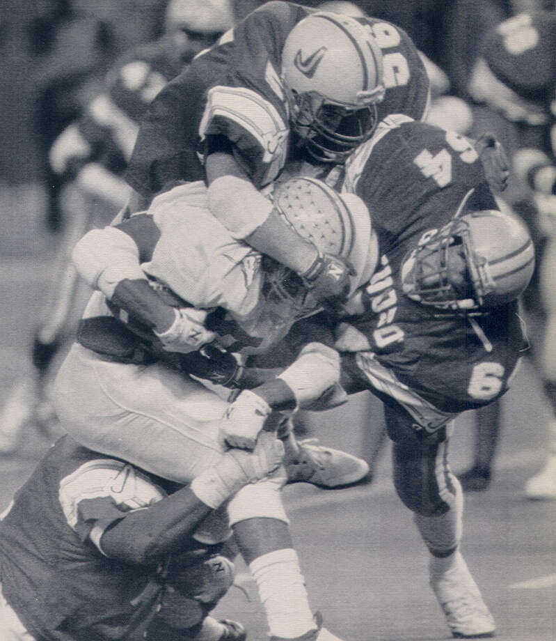 Judson linebacker Mark Soto (right) helps take down a Marshall back during the 5A state title game in 1990. Photo: Express-News File Photo