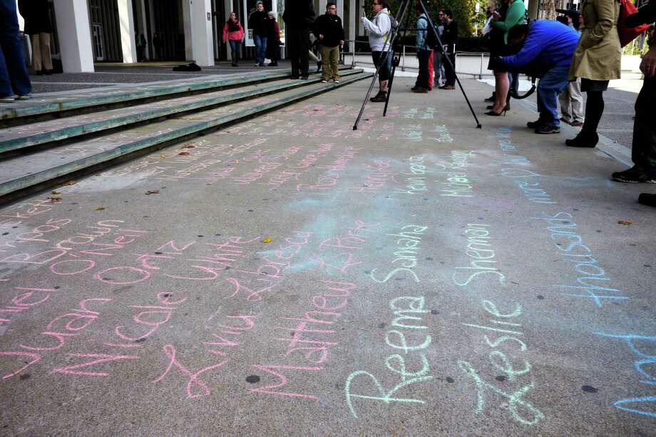 The names of children killed in gun violence are written in chalk during a rally to condemn gun violence Thursday, Oct. 24, 2013, at University at Albany in Albany, N.Y.  (Paul Buckowski / Times Union) Photo: Paul Buckowski / 00024372A