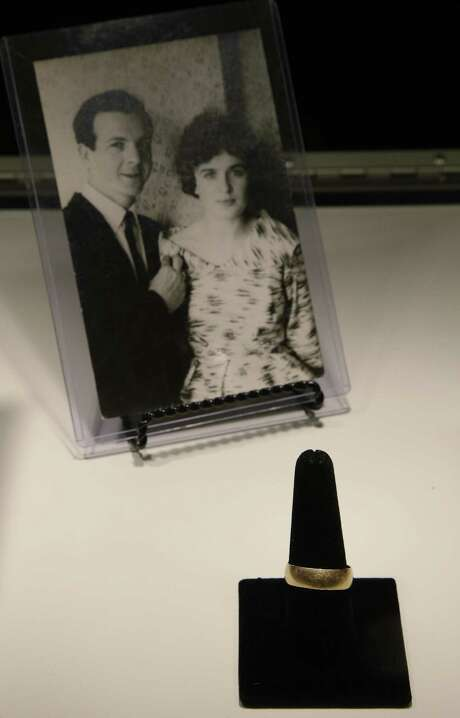 Lee Harvey Oswald's wedding ring, which he left in a cup on the dresser the morning of the assassination of President John F. Kennedy, is part of a themed JFK memorabilia auction in Boston. The picture behind the ring is of Lee Harvey Oswald and his wife, Marina Oswald. Photo: Stephan Savoia / Associated Press