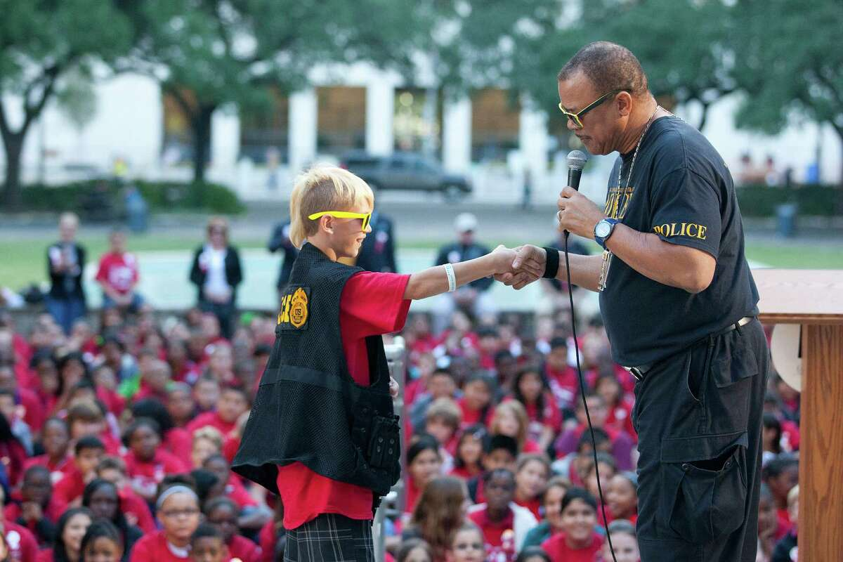 Jesse Dougan, 12, a fifth grader at Drew Intermediate School, shakes the hand of DEA special agent Edmund Collins after Dougan took an oath to not use drugs as more than 500 middle school students from the greater Houston area attended the 20th Annual Enrique