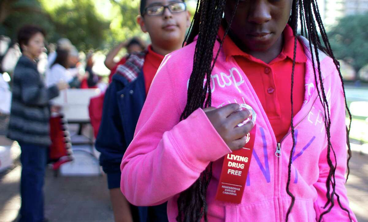 """Students put on """"Living Drug Free"""" ribbons as more than 500 middle school students from the greater Houston area attended the 20th Annual Enrique """"Kiki"""" Camarena Red Ribbon Rally promoting a drug free lifestyle outside City Hall Thursday, Oct. 24, 2013, in Houston. The rally included an anti-drug presentation on the steps of City Hall, speakers, and a mock youth city council session where they passed a series of drug free ordinances in city council chambers."""