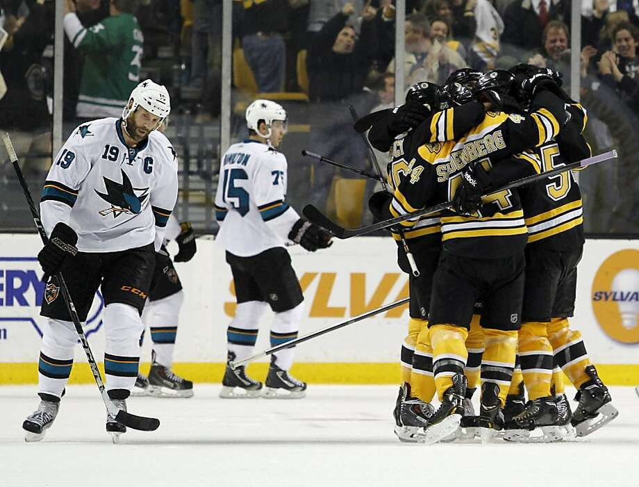 The dejection of Joe Thornton (left) contrasts with the Bruins' joy after their game-winner. Photo: Mary Schwalm, Associated Press