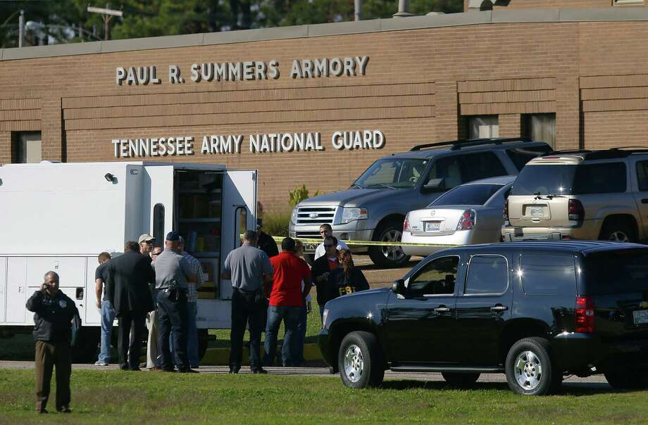 Law enforcement and military personnel investigate the scene where shootings occurred at an armory outside a U.S. Navy Base in Millington, Tenn. A spokesperson says two military reserve members were shot with wounds not life-threatening. Photo: Lance Murphey / Associated Press