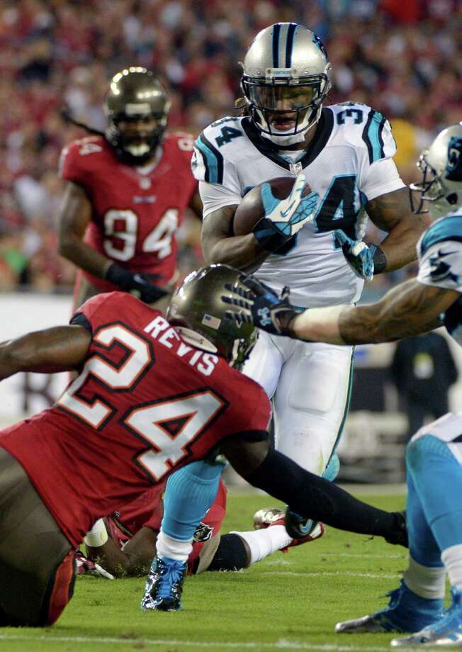 Carolina Panthers running back DeAngelo Williams (34) gets past Tampa Bay Buccaneers cornerback Darrelle Revis (24) for a 12-yard touchdown run during the first half of an NFL football game in Tampa, Fla., Thursday, Oct. 24, 2013. (AP Photo/Phelan M. Ebenhack) ORG XMIT: TPS207 Photo: Phelan M. Ebenhack / FR121174 AP