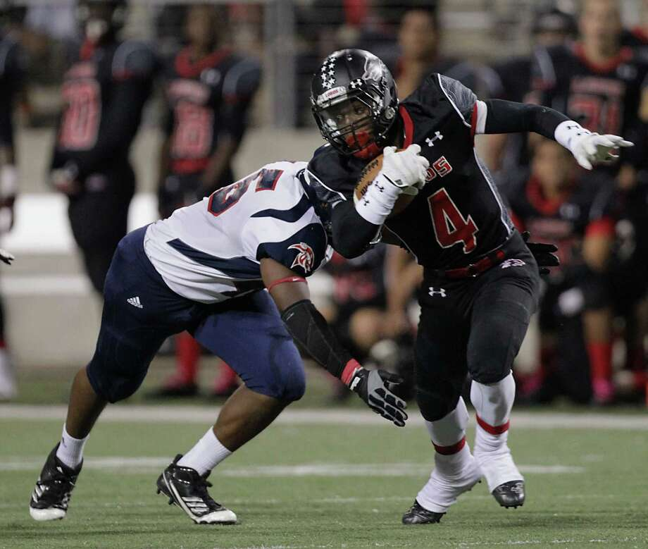 Cypress Springs' James Ware left, tackles Langham Creek's Dominique Harris right, during the first quarter of high school football game action at the Berry Center Thursday, Oct. 24, 2013, in Cypress. Photo: James Nielsen, Houston Chronicle / © 2013  Houston Chronicle