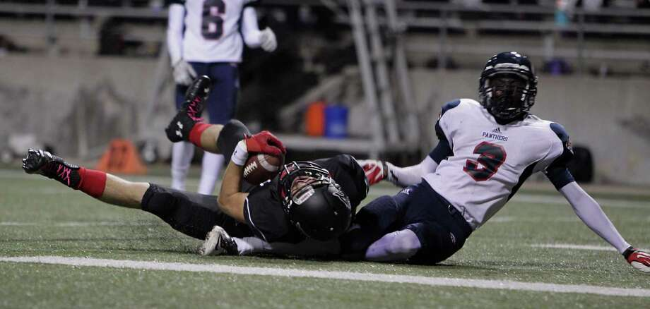 Langham Creek's Bryce Elkin left, rolls in the end zone with Cypress Springs' Lawrance Ghansah right, after Elkin's touchdown during the second quarter of high school football game action at the Berry Center Thursday, Oct. 24, 2013, in Cypress. Photo: James Nielsen, Houston Chronicle / © 2013  Houston Chronicle
