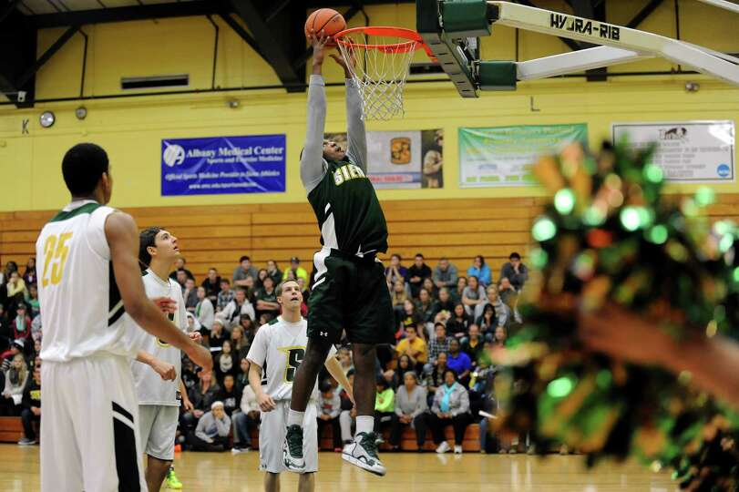 Siena's Maurice White, center, goes to the hoopl during a basketball scrimmage for Siena Madness on