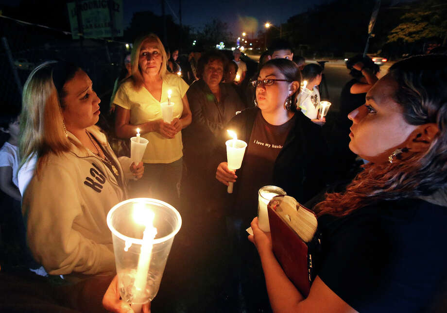 Priscilla Ledesma (right center) answers questions about her sister as supporters gather with family members on October 24, 2013 in the 3900 block of Culebra to hold a candle light vigil and prayer for Sharon Ledesma who was hit by a car Wednesday morning as she crossed Culebra.   on October 24, 2013. Photo: TOM REEL