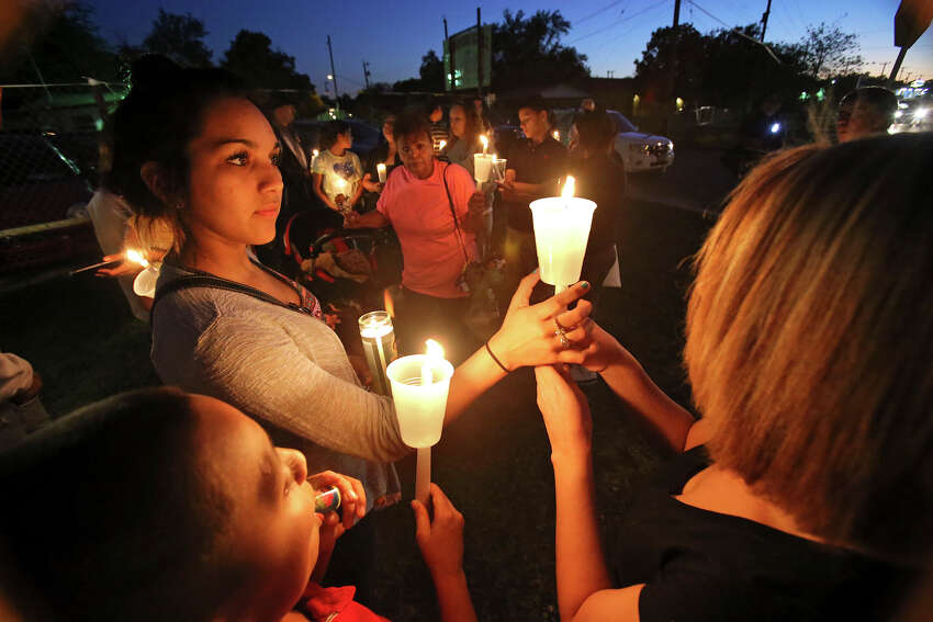 Abby Faz (left) steadies a candle for Valerie Guzman as Raymond Cano watches as supporters gather with family members on October 24, 2013 in the 3900 block of Culebra to hold a candle light vigil and prayer for Sharon Ledesma who was hit by a car Wednesday morning as she crossed Culebra.