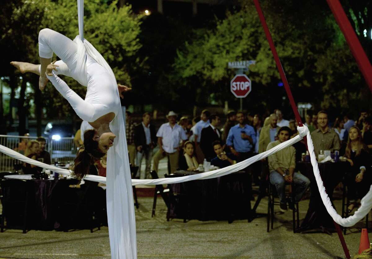 Aerialist Laura DiPasquale performs during a block party thrown by the Ghost Light Society, which aims to get young professionals involved at the Tobin Center for the Performing Arts.