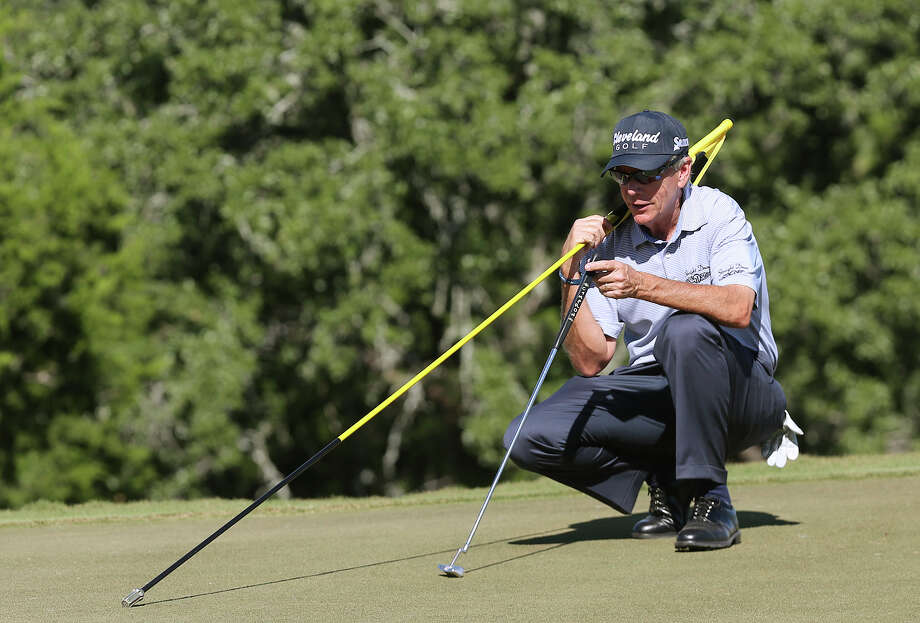 Larry Mize of Columus, Georgia, gives out tips while on the 14th green during the AT&T Championship Pro-Am at the Canyons Course of TPC San Antonio, Thursday, Oct. 24, 2013. Photo: Jerry Lara, San Antonio Express-News / ©2013 San Antonio Express-News
