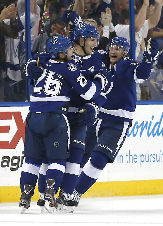 Martin St. Louis (26) is congratulated after scoring the game-winner in overtime. Photo: Reinhold Matay, Associated Press