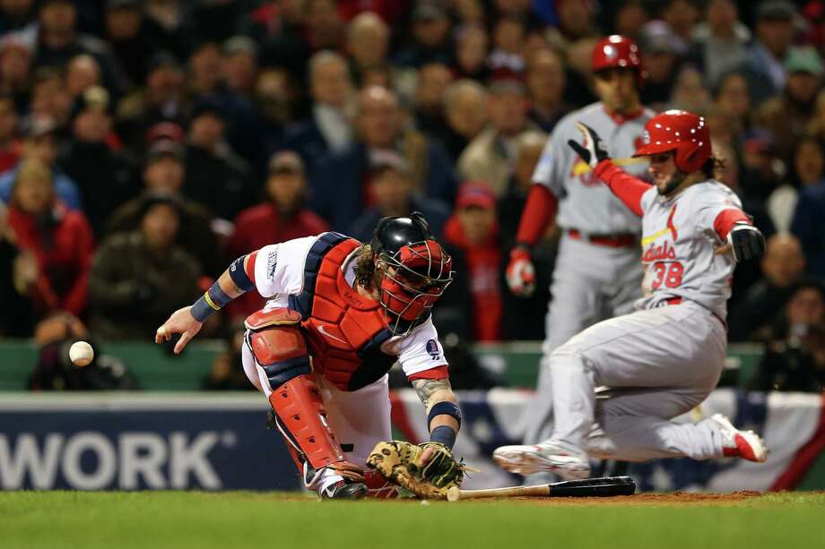 The Cardinals' Pete Kozma (right) slides into home as Red Sox catcher Jarrod Saltalamacchia loses the ball during Game 2 on Thursday. St. Louis snapped Boston's nine-game winning streak in the World Series. Photo: Elsa / Getty Images