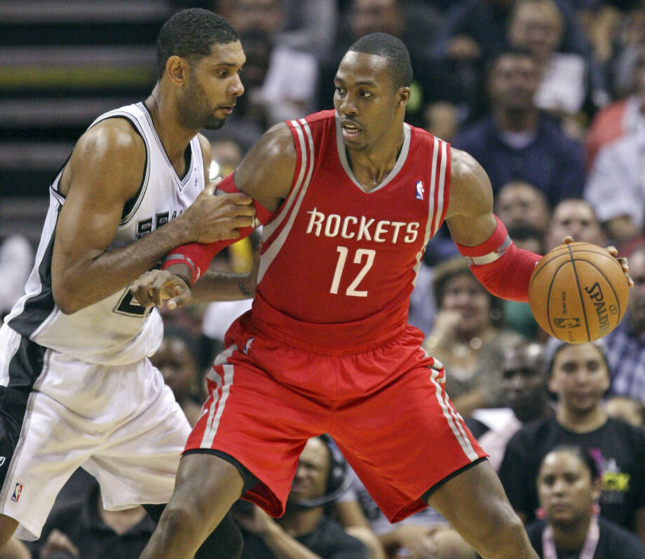 Tim Duncan defends new Rockets center Dwight Howard, who had 15 points and 16 boards, in the first half at the AT&T Center. Photo: Edward A. Ornelas / San Antonio Express-News