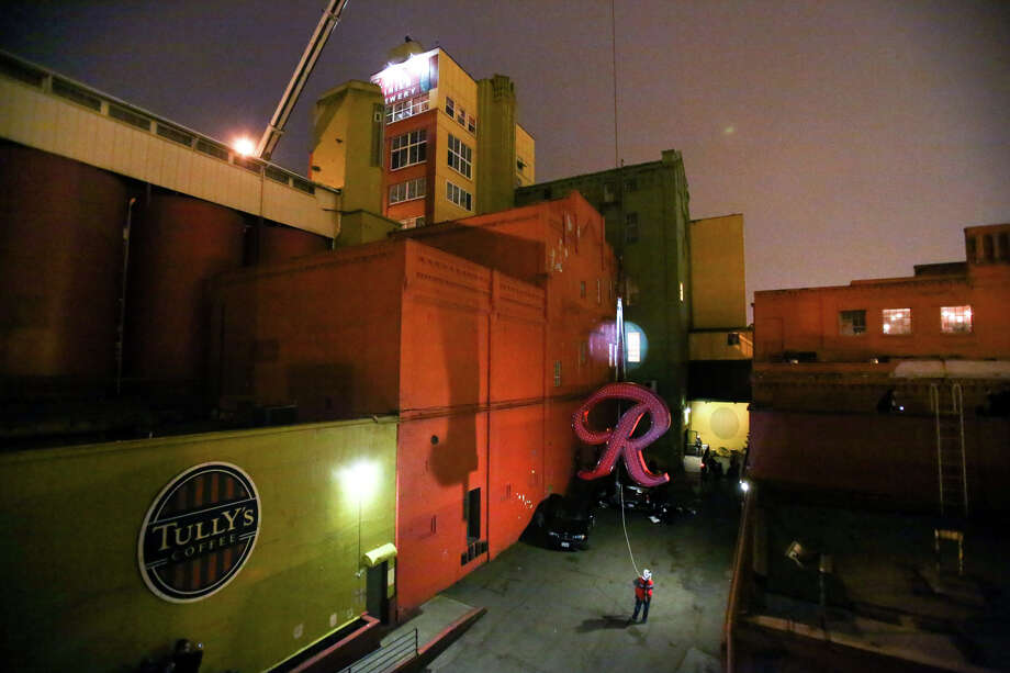 "The Rainier Beer ""R"" begins its journey up as it is hoisted to its spot at the top of the old Rainier Brewery during a community celebration. The ""R"" replaced the Tully's Coffee ""T"" which had been on the building since 2000. The ""R"" had been a Seattle icon for 50 years before the green ""T"" took its place. Photographed on Friday, Oct. 25, 2013. Photo: JOSHUA TRUJILLO, SEATTLEPI.COM / SEATTLEPI.COM"