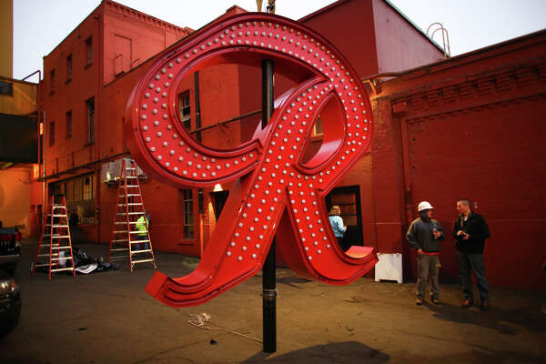 "The Rainier Beer ""R"" is ready to be hoisted to its spot at the top of the old Rainier Brewery during a community celebration. The ""R"" replaced the Tully's Coffee ""T"" which had been on the building since 2000. The ""R"" had been a Seattle icon for 50 years before the green ""T"" took its place. Photographed on Friday, October 25, 2013."