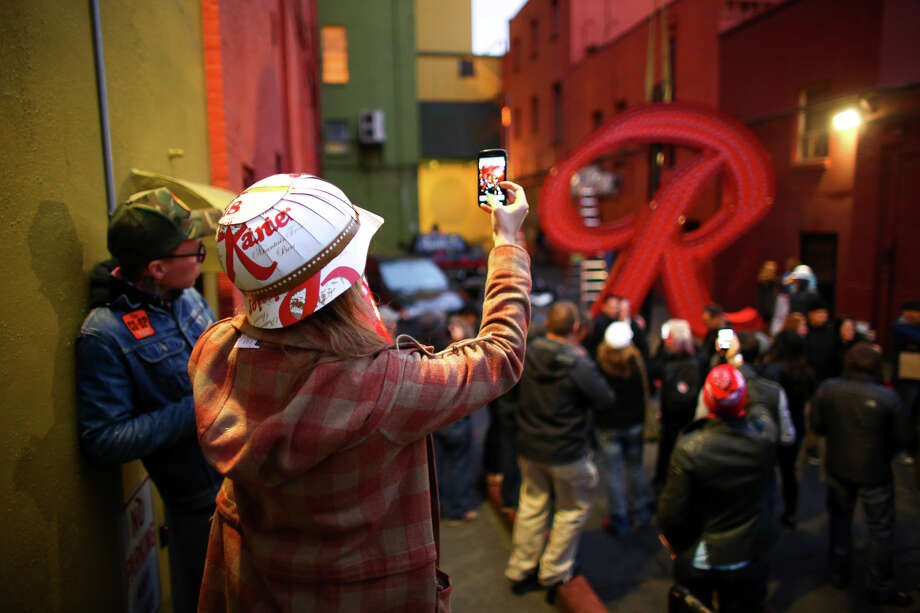 "People take photos before the Rainier Beer ""R"" is hoisted to its spot at the top of the old Rainier Brewery during a community celebration. The ""R"" replaced the Tully's Coffee ""T"" which had been on the building since 2000. The ""R"" had been a Seattle icon for 50 years before the green ""T"" took its place. Photographed on Friday, October 25, 2013. Photo: JOSHUA TRUJILLO, SEATTLEPI.COM / SEATTLEPI.COM"