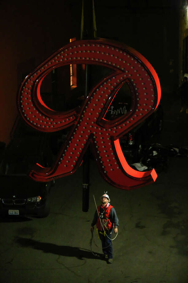 "The Rainier Beer ""R"" is hoisted Friday to its spot at the top of the old Rainier Brewery during a community celebration. The ""R"" replaced the Tully's Coffee ""T"" which had been on the building since 2000. The ""R"" had been a Seattle icon for 50 years before the green ""T"" took its place. Photo: JOSHUA TRUJILLO, SEATTLEPI.COM / SEATTLEPI.COM"