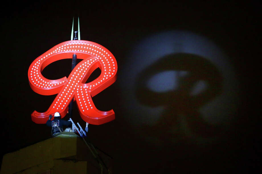 """The Rainier Beer """"R"""" casts a shadow on the clouds as it is raised to the top of the old Rainier Brewery during a community celebration. The """"R"""" replaced the Tully's Coffee """"T"""" which had been on the building since 2000. The """"R"""" had been a Seattle icon for 50 years before the green """"T"""" took its place. The iconic sign was rebuilt by the team at Western Neon. (Photographed on Friday, October 25, 2013.) Photo: JOSHUA TRUJILLO, SEATTLEPI.COM / SEATTLEPI.COM"""