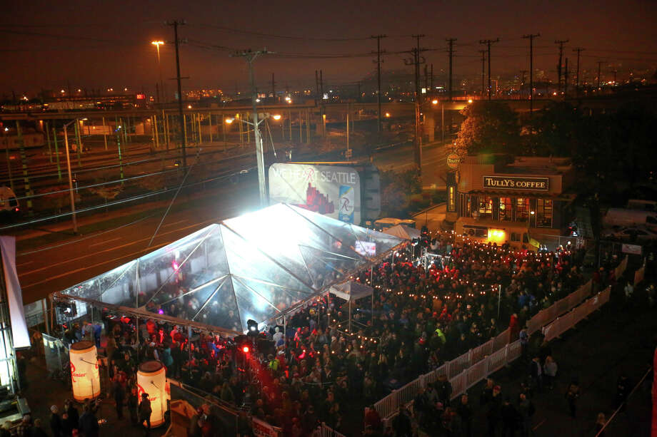 "People gather in a party tent as the Rainier Beer ""R"" is hoisted Friday to its spot at the top of the old Rainier Brewery during a community celebration. The ""R"" replaced the Tully's Coffee ""T"" which had been on the building since 2000. The ""R"" had been a Seattle icon for 50 years before the green ""T"" took its place. Photo: JOSHUA TRUJILLO, SEATTLEPI.COM / SEATTLEPI.COM"