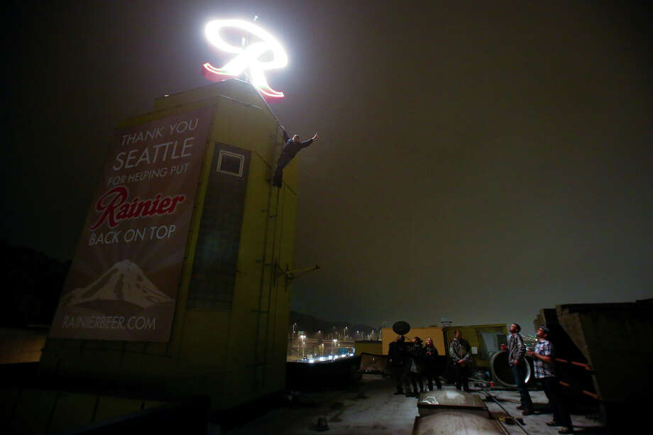 "People gather on the roof shortly after the Rainier Beer ""R"" was hoisted to its spot at the top of the old Rainier Brewery Friday during a community celebration. The ""R"" replaced the Tully's Coffee ""T"" which had been on the building since 2000. The ""R"" had been a Seattle icon for 50 years before the green ""T"" took its place.  Photo: JOSHUA TRUJILLO, SEATTLEPI.COM / SEATTLEPI.COM"