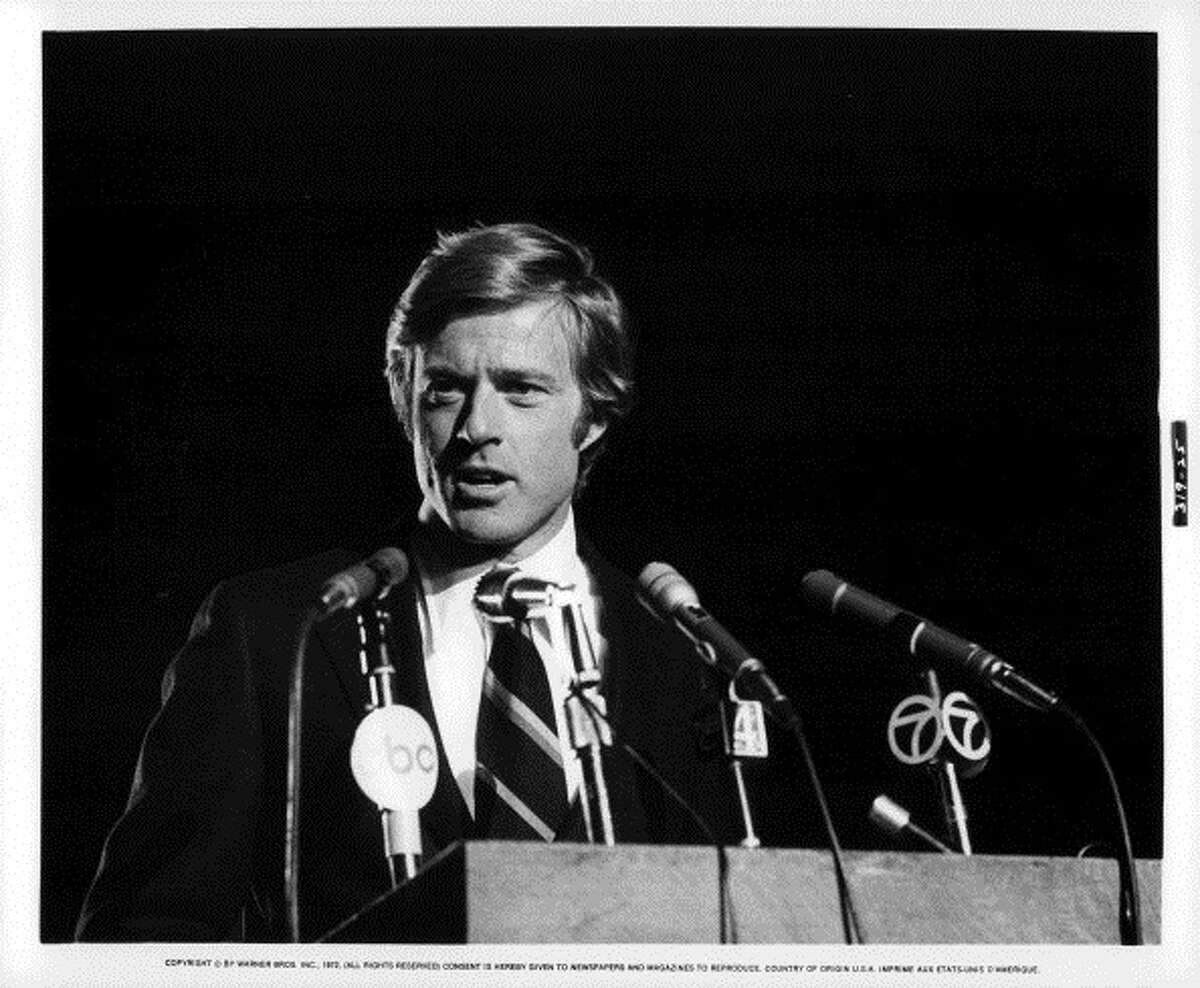 Robert Redford stands behind microphones in a scene from the film 'The Candidate', 1972. (Photo by Warner Brothers/Getty Images)