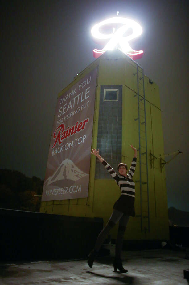 "Dancer Emma Lavin strikes a pose Friday after the Rainier Beer ""R"" is hoisted to its spot at the top of the old Rainier Brewery during a community celebration. The ""R"" replaced the Tully's Coffee ""T"" which had been on the building since 2000. The ""R"" had been a Seattle icon for 50 years before the green ""T"" took its place.  Photo: JOSHUA TRUJILLO, SEATTLEPI.COM / SEATTLEPI.COM"