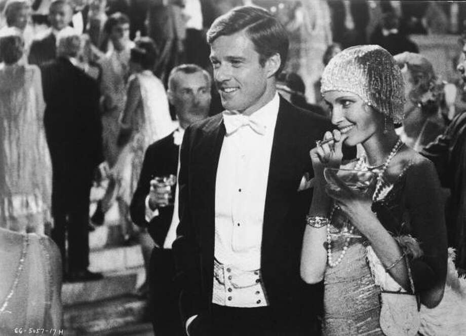 American actors Robert Redford, as Jay Gatsby, and Mia Farrow, as Daisy Buchanan, smile at a well-to-do party in a scene from 'The Great Gatsby,' based on the novel by F. Scott Fitzgerald and directed by Jack Clayton, 1974. (Photo by Paramount Pictures/Courtesy of Getty Images) Photo: Paramount Pictures, Getty Images / Moviepix