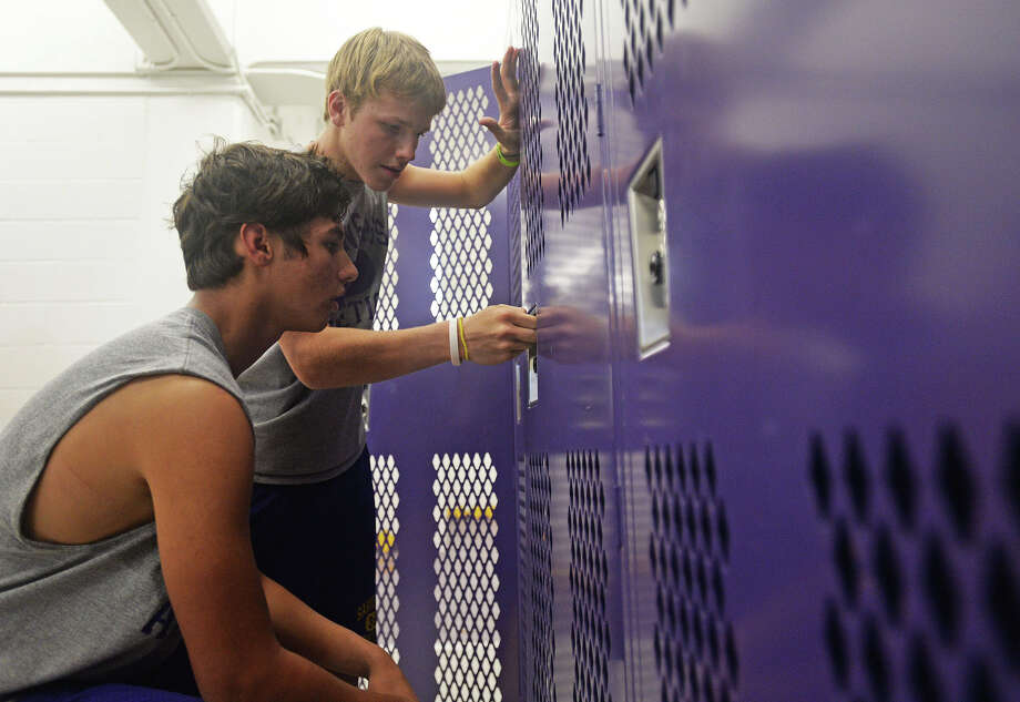 Sabine Pass football players, freshman Luis Rojas, left, and sophomore Alex Rouly, unlock their lockers in there  newly constructed field house. Since 2008, the Sabine Pass football team has been without a field house due to Hurricane Ike, which destroyed the previous field house in 2008. Michael Rivera/ The Enterprise