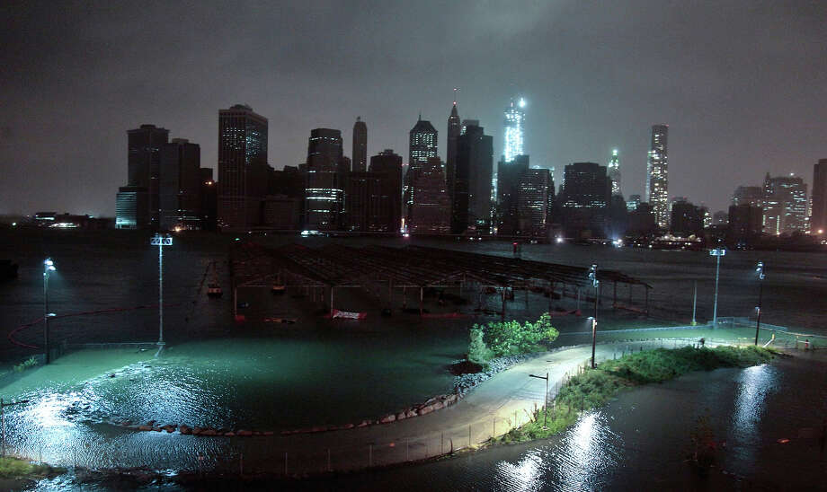 This combination of Oct. 29, 2012 and Oct. 17, 2013 photos shows a darkened lower Manhattan during Superstorm Sandy as seen from the Brooklyn Heights promenade in the Brooklyn borough of New York and the same view nearly a year later. Photo: Bebeto Matthews, AP / THE ASSOCIATED PRESS2012