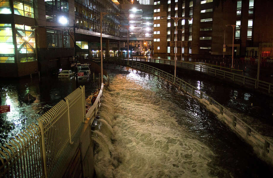 This combination of Oct. 29, 2012 and Oct. 20, 2013 photos shows sea water flooding the entrance to the Brooklyn Battery Tunnel in New York as Superstorm Sandy struck the city and traffic entering nearly a year later. Photo: John Minchillo, AP / AP2012