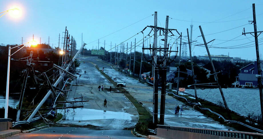 This combination of Oct. 30, 2012 and Oct. 22, 2013 photos shows downed power lines and a battered road smashed by Superstorm Sandy in Seaside Heights, N.J. and traffic flowing at the same site nearly a year later. Photo: Julio Cortez, AP / AP2012