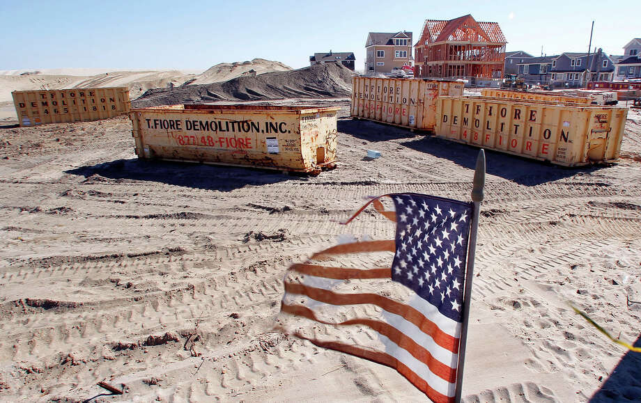 This combination of Thursday, April 25, 2013 and Sunday, Oct. 13, 2013 photos shows U.S. flags at a site in Brick, N.J., around the burned remains of more than 60 small bungalows at Camp Osborn which were destroyed during Superstorm Sandy and the same area nearly six months later. Photo: Mel Evans, AP / A2013