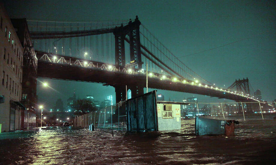 This combination of Monday, Oct. 29, 2012 and Thursday, Oct. 17, 2013 photos shows flooded streets under the Manhattan Bridge in the Dumbo section of Brooklyn, New York in the wake of Superstorm Sandy and the same site nearly a year later. Photo: Bebeto Matthews, AP / AP2012