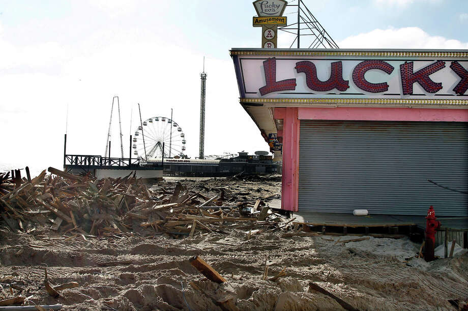 This combination of Thursday, Nov. 22, 2012 and Sunday, Oct. 13, 2013 photos shows debris left by Superstorm Sandy where the boardwalk had been in front of Lucky Leo's arcade in Seaside Heights, N.J. and people walking at the rebuilt area nearly a year later. Photo: Mel Evans, AP / A2012