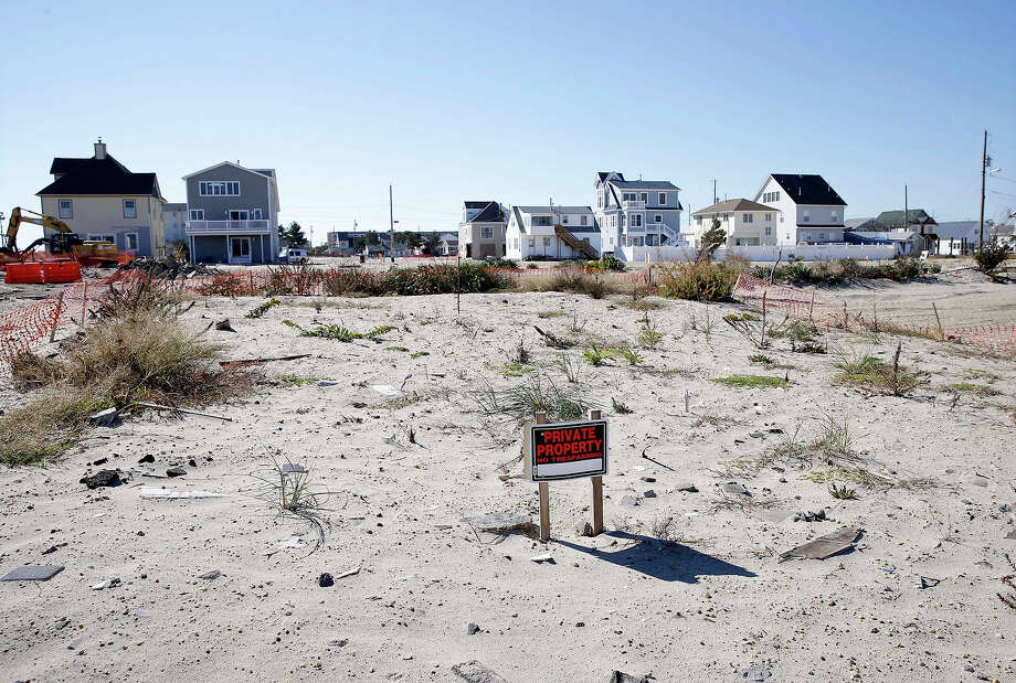 This combination of Thursday, April 25, 2013 and Sunday, Oct. 13, 2013 photos shows homes destroyed by Superstorm Sandy at Ortley Beach in Toms River, N.J. and an empty lot in the area six months later. Photo: Mel Evans, AP / A2013