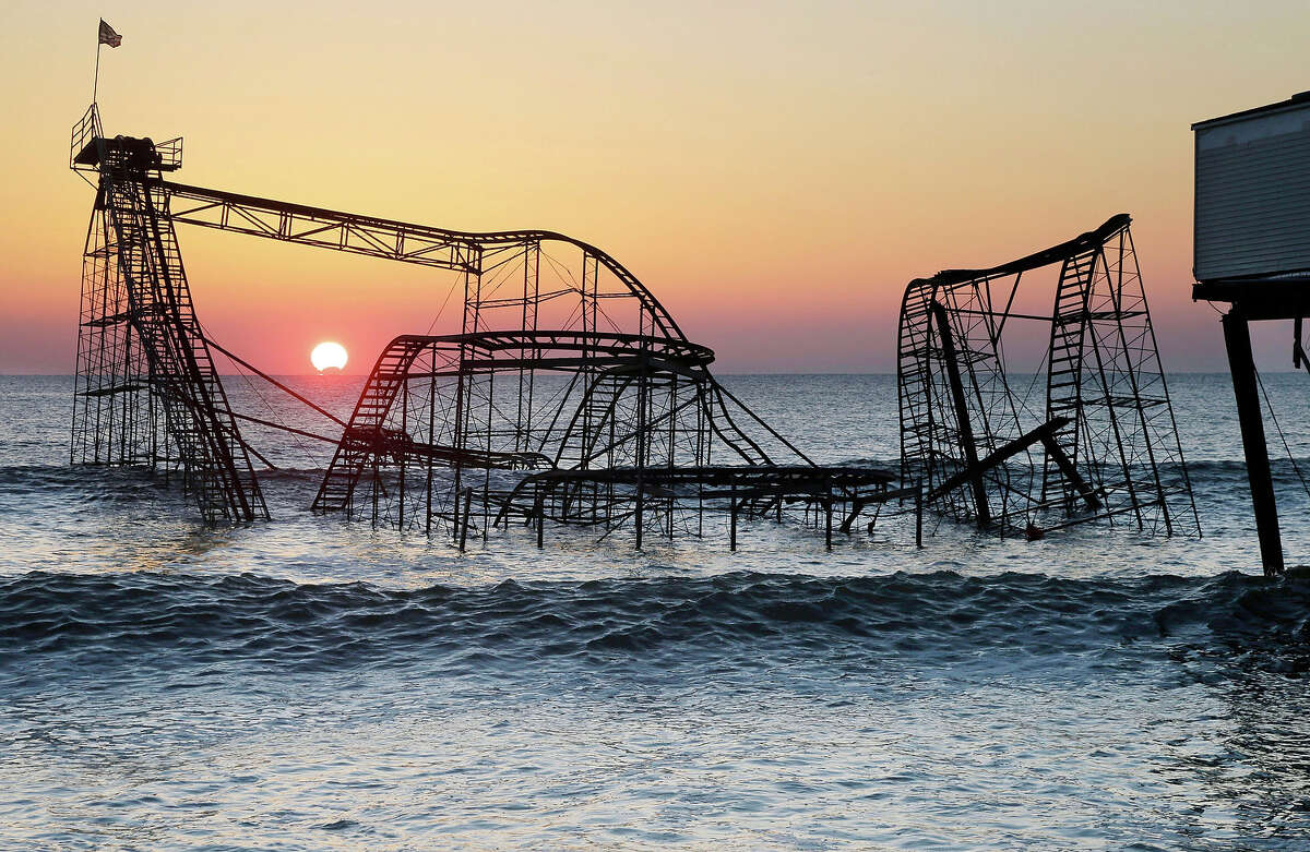 In this combination of Monday, Feb. 25, 2013 and Sunday, Oct. 13, 2013 photos, the sun rises in Seaside Heights, N.J., behind the Jet Star Roller Coaster which had been sitting in the ocean after part of the Casino Pier was destroyed during Superstorm Sandy, and the empty site nearly a year after the storm.