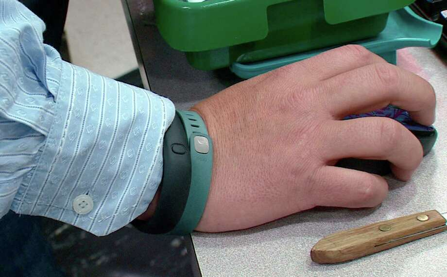 This photo from video taken Oct. 9, 2013 shows the wrist of Tim Davis wearing his FitBit, green, and Nike FuelBand, black, devices he uses to track his physical activity and habits, in New Brighton, Pa. Photo: Noel Waghorn, Associated Press / Associated Press