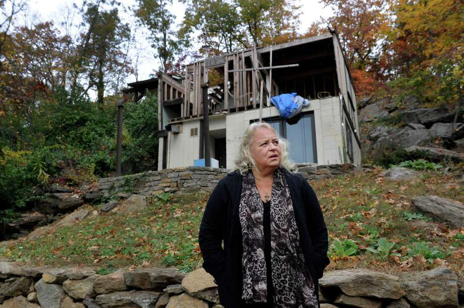 Diane Davison walks her property overlooking Candlewood Lake in Danbury, Conn., Wed. Oct. 23, 2013, where her house was destroyed by high winds and falling trees during Hurricane Sandy last year. Photo: Carol Kaliff / The News-Times