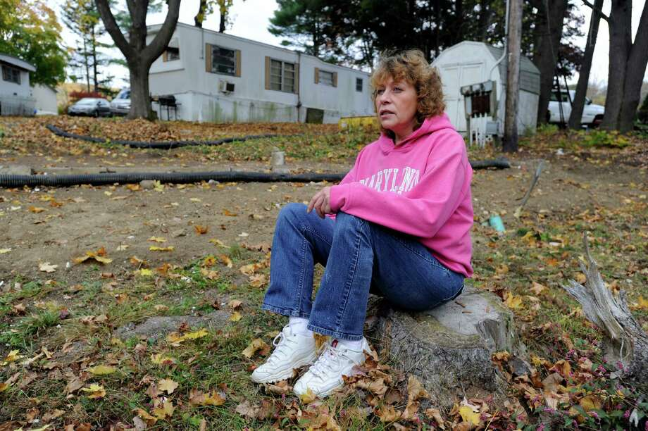 Kathleen Wade home was destroyed during Hurricane Sandy when trees fell on her trailer in Newtown, Conn. Sitting on stump of one of those trees, she talks about her experience Friday, Oct. 25, 2013. Photo: Carol Kaliff / The News-Times