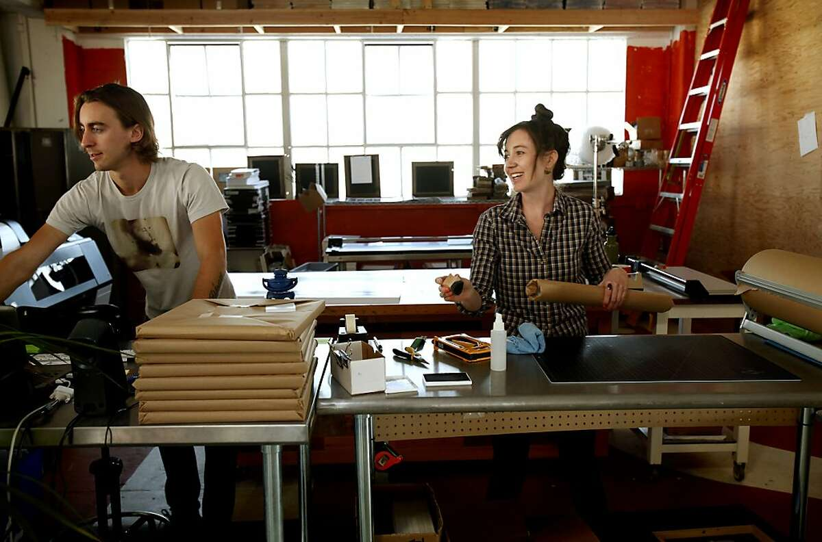 Xandre Borghetti, left, and Lauren Douglas work at the Social Print Studio in San Francisco, Calif., on Thursday, October 17, 2013. The company offers many perks to its employees, including nap boxes, in-house cooked meals, a music studio, and the opportunity to choose one of its taxidermy animals as a spirit animal.