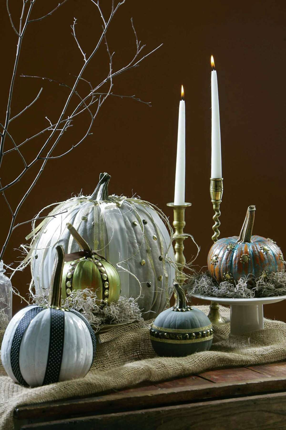 Real pumpkins can be turned into boutique-like deocrations with spray paint, acrylics and a few other accessories such as tacks from a hardware store and ribbons. (Jim Barcus/Kansas City Star/MCT)